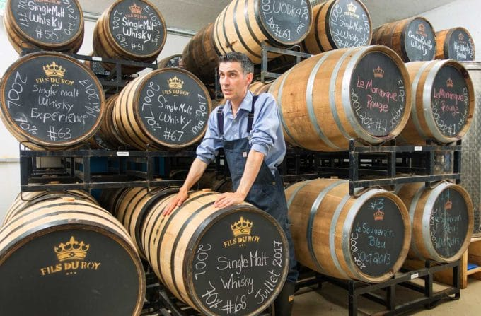 Sebastian Roy in front of Whiskey and other Spirit barrels at his distillery in