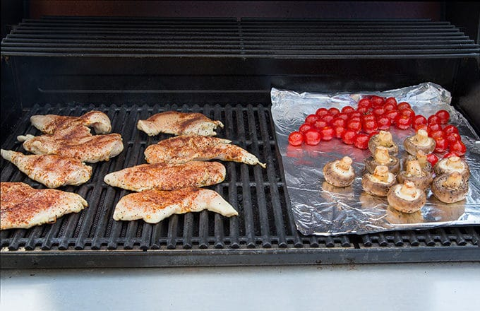 seasoned chicken breasts on a barbecue grill, with cherry tomatoes and mushrooms on foil next to the chicken