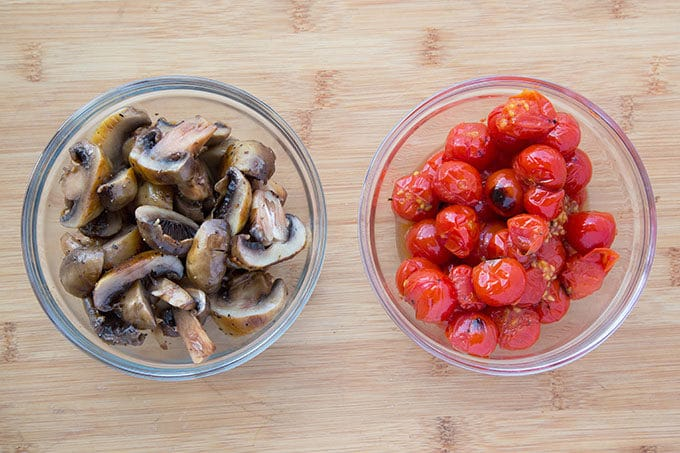 glass bowls of grilled mushrooms and tomatoes on a wooden cutting board