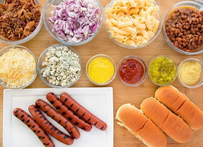 bowls of toppings for a hot dog bar with grilled ball park hot dogs on a white platter with hot dog rolls next to it all sitting on a wooden cutting board