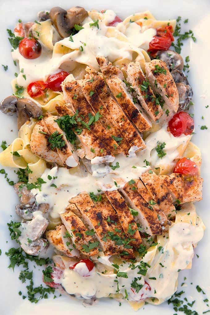 slices of seasoned grilled boneless skinless chicken breast sitting on top of Pappardelle with alfredo sauce, grilled cherry tomatoes and mushrooms sprinkled with chopped parsley on a white serving platter