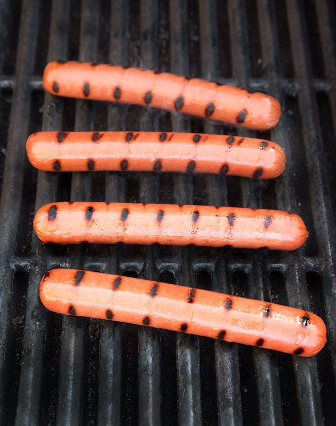 hot dogs with grill marks cooking on a barbecue grill