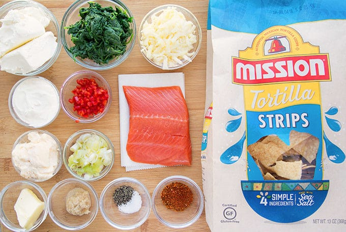 ingredients to make salmon dip on a wooden cutting board next to a bag of mission tortilla chips