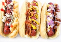 Grilled Hot Dogs on Potato Rolls with different toppings sitting on a White Platter