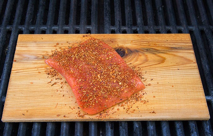 Uncooked Seasoned Salmon on Plank on grill grates