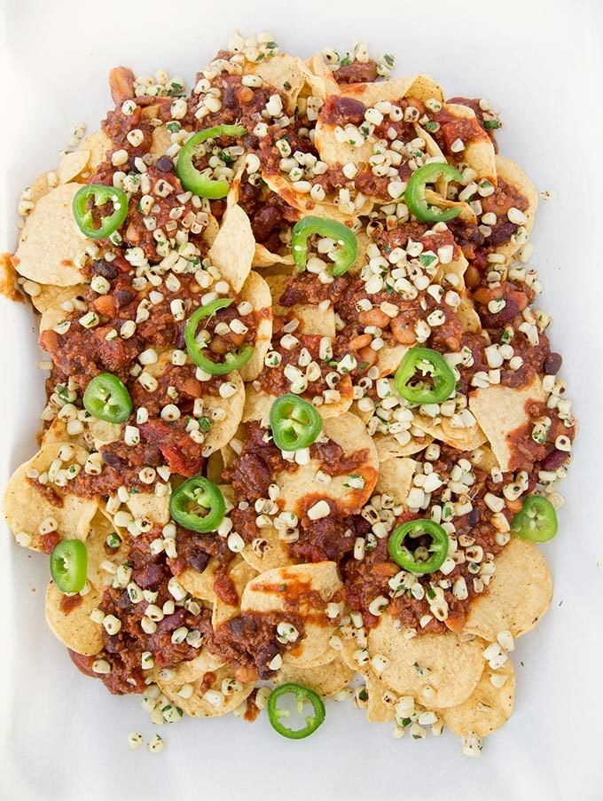 corn chips topped with chili and beans, roasted yellow corn kernels, and sliced jalapeños