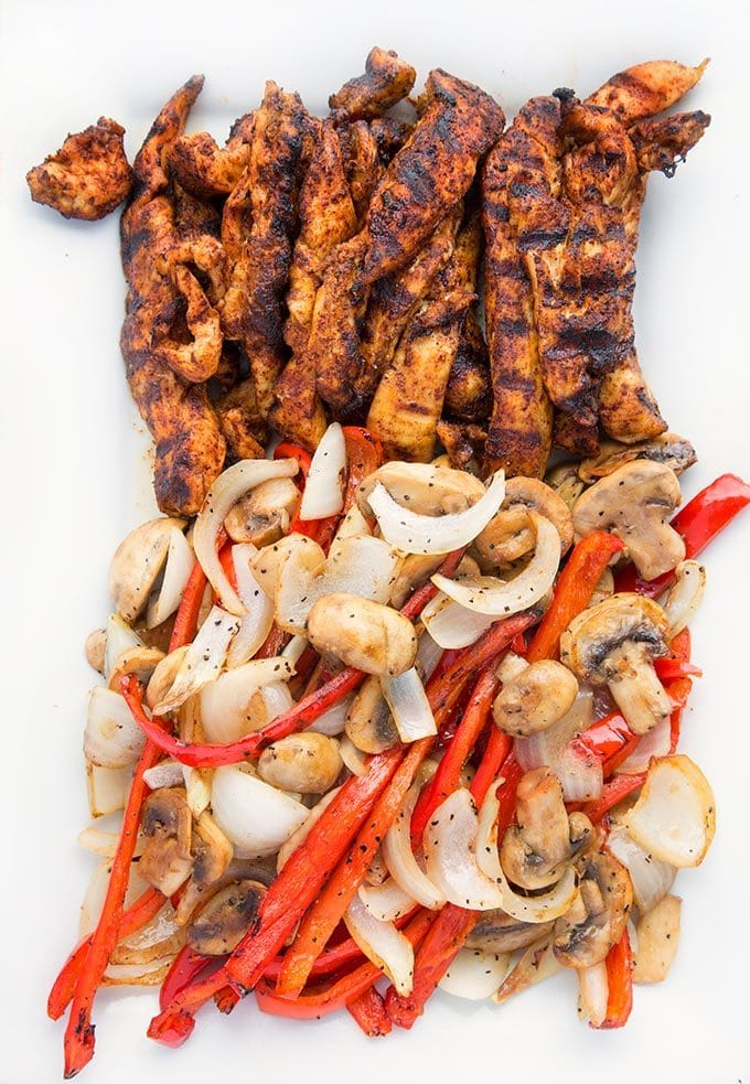 seaspmed grilled chicken strips next to grilled sliced red peppers, onions and mushrooms on a rectangular white platter