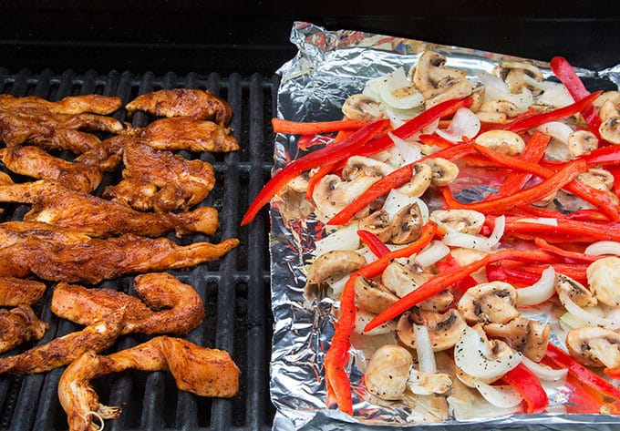 seasoned chicken strips on a grill next to sliced red peppers, onions and mushrooms on a foil sheet on top of the grill