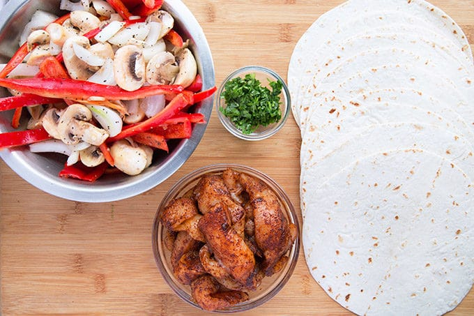Stainless steel bowl of sliced red peppers, onion and mushrooms mixed together, glass bowl of seasoned chicken strips, small bowl of chopped cilantro and a stack of tortillas spread out on a wooden cutting board
