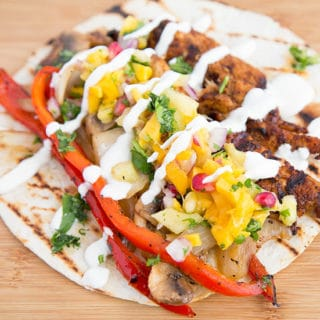 a grilled chicken fajitas topped with pineapple salsa and crema sitting on a wooden cutting board