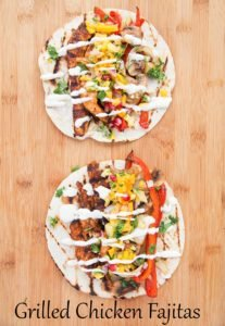 two grilled chicken fajitas topped with pineapple salsa and crema sitting on a wooden cutting board