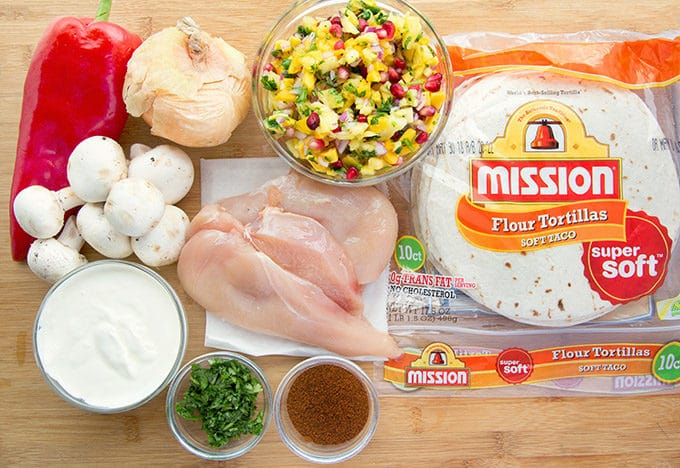 ingredients to make grilled chicken fajitas, including pineapple-mango salsa, lime crema and a [ackage of Mission flour tortillas