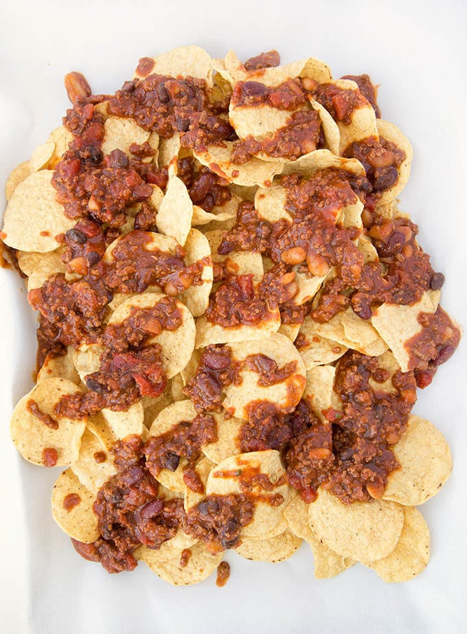 round corn chips topped with 4 bean chili sitting on white parchment paper