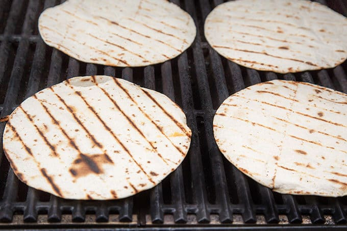 4 flour tortillas with grill marks sitting directly on grill grates