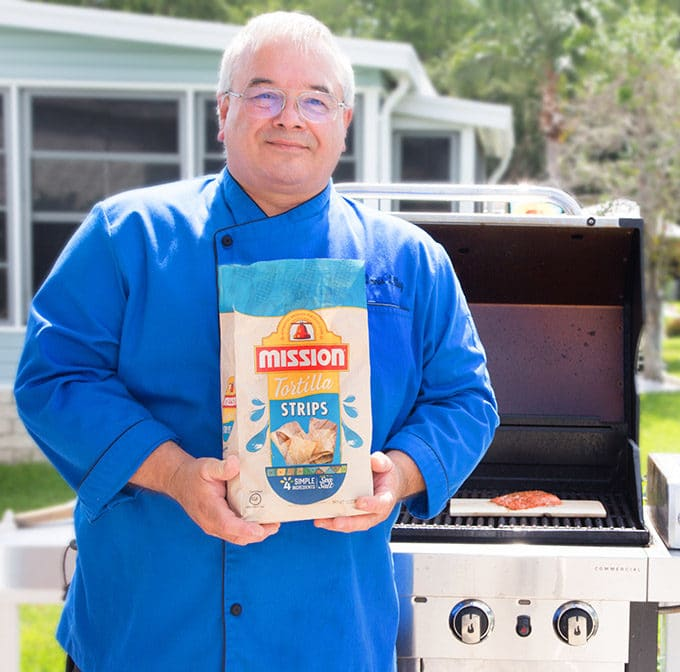 Chef Dennis a bright blue chef coat holding a bag of Mission tortilla chips standing in front of a grill