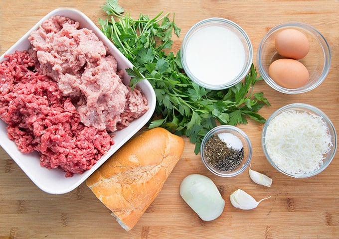 ingredients to make Italian meatballs sitting on a wooden cutting board