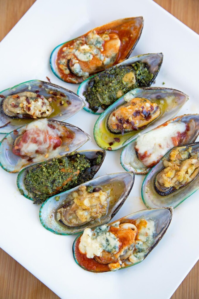 mussels topped with five toppings on a white platter