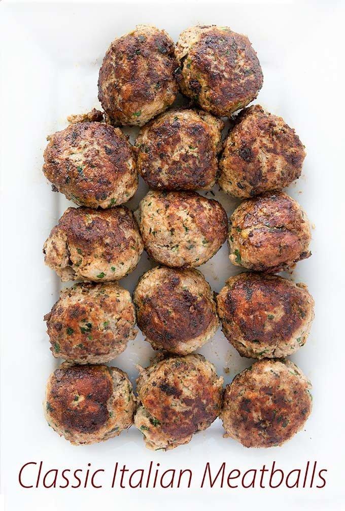 cooked Italian meatballs sitting on a rectangular white serving platter