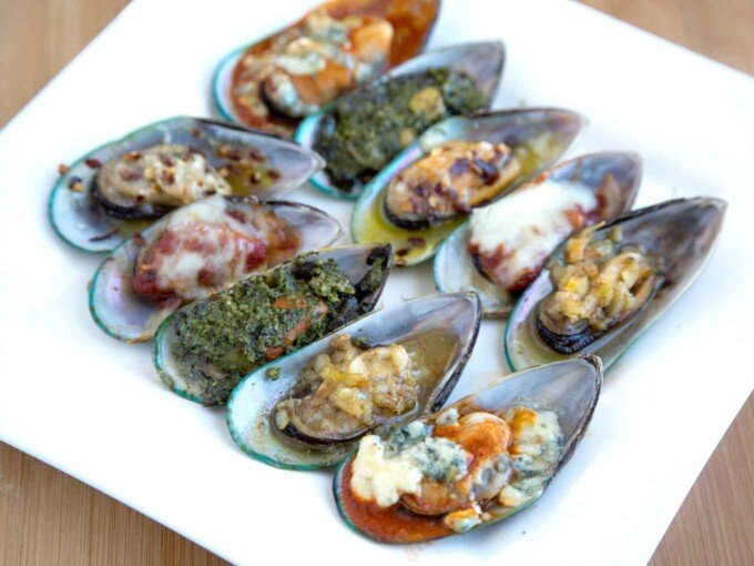 mussels with five different toppings on a white platter