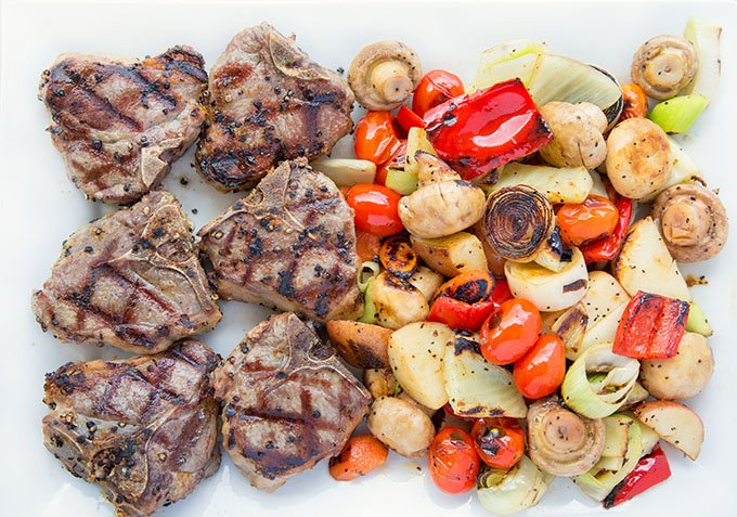grilled lamb and grilled vegetables on a white plater