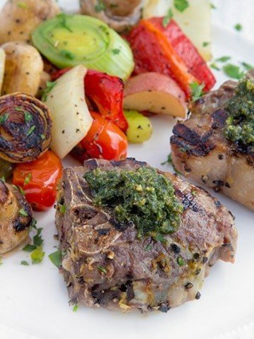 grilled lamb chops with a mint pesto on a white plate with grilled vegetables
