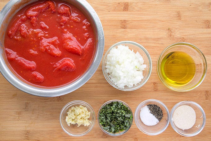 ingredients to make tomato sauce in glass bowls sitting on a wooden cutting board
