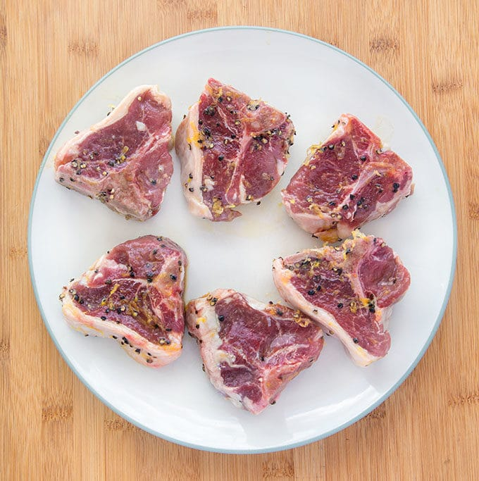 marinated lamb chops on a white plate on top of a wooden cutting board