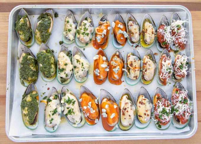 unbaked mussels with five different toppings on a half sheet pan