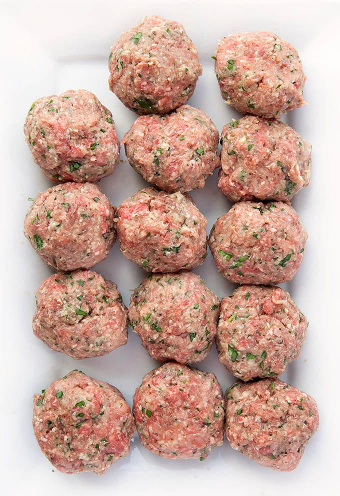 raw meatballs place in rows on a rectangular white serving dish