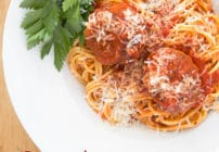¾'s view of a white bowl filled with spaghetti and meatballs with a sprig of parsley in the corner of the bowl, sitting on a wooden cutting board