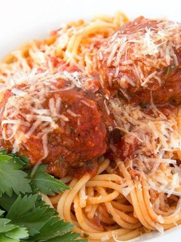 white bowl of spaghetti with two meatballs topped with grated romano cheese, with a sprig of Italian parsley in the bottom left corner