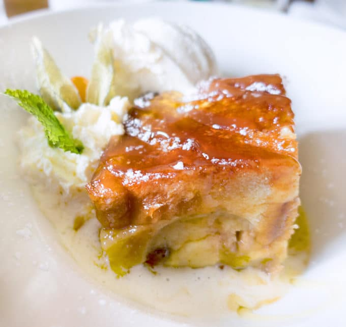 bread and butter pudding on a white plate with vanilla ice cream and sauce served at the Abbey Tavern in Howth Ireland