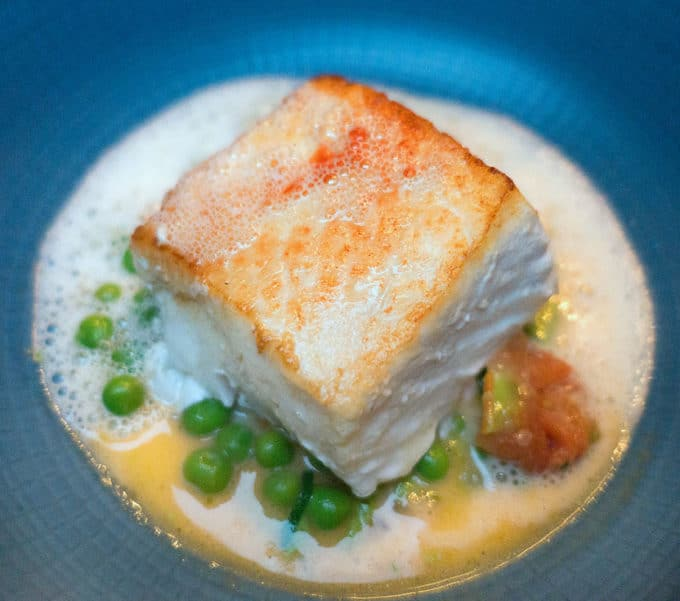 pan seared halibut with a white sauce and fresh peas on a blue plate in Dublin Ireland at Ely's Wine Bar