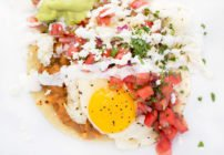 Huevos Rancheros with a sunny side up fried egg sitting on a white plate