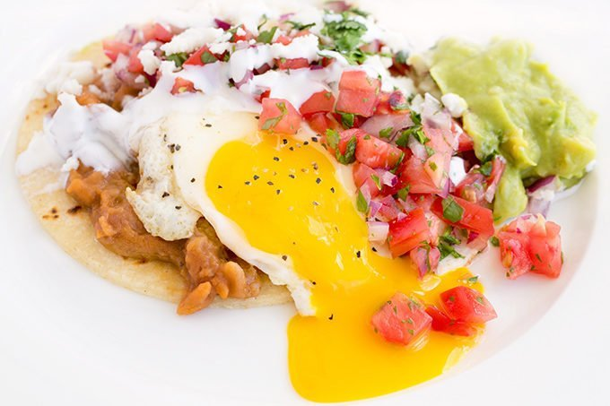 Huevos Rancheros with yolk running on a white plate