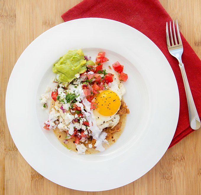 huevos rancheros on a white plate view from above the plate with a dark red napkin and fork on a wooden cutting board