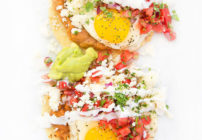 2 portions of huevos rancheros on a white platter