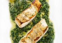 2 fillets of pan seared halibut sitting on a bed of creamed spinach on a white platter with 2 lemon slices in the upper left hand corner
