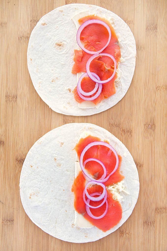 two flour tortillas with cheese , smoked salmon and sliced red onions sitting on a cutting board