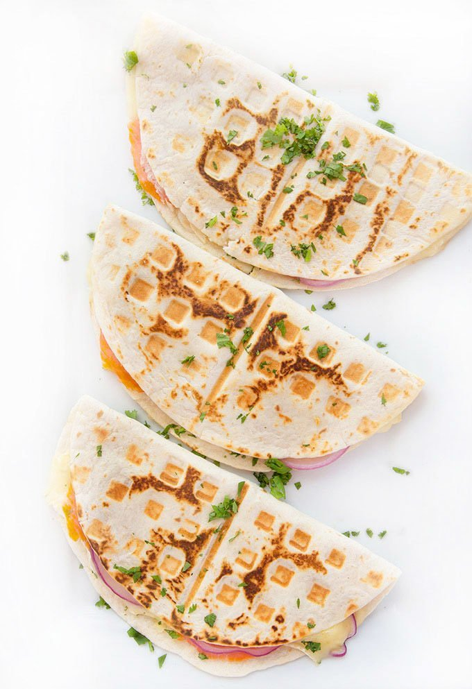 3 nicely browned smoked salmon quesadillas sitting on a white platter