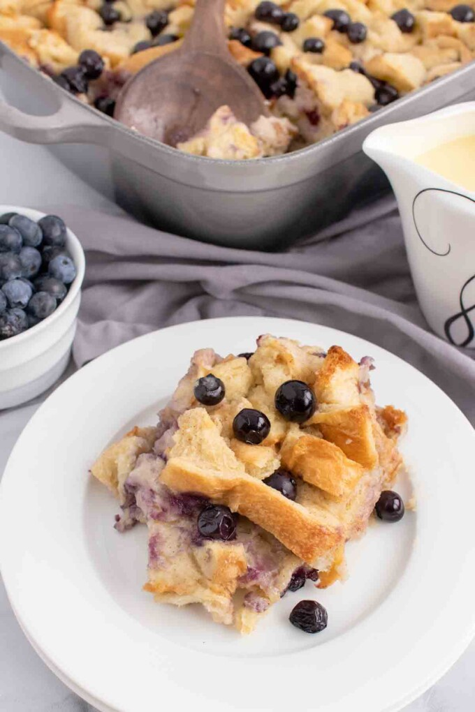 portion fo blueberry bread pudding on a white plate without the cream anglais