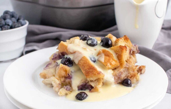 blueberry bread pudding on a white plate with creme anglais