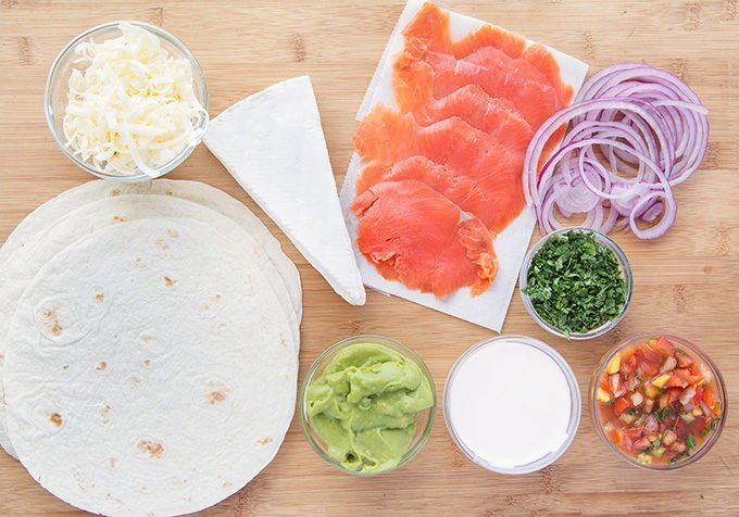 ingredients to make smoked salmon quesadillas sitting on a wooden cutting board