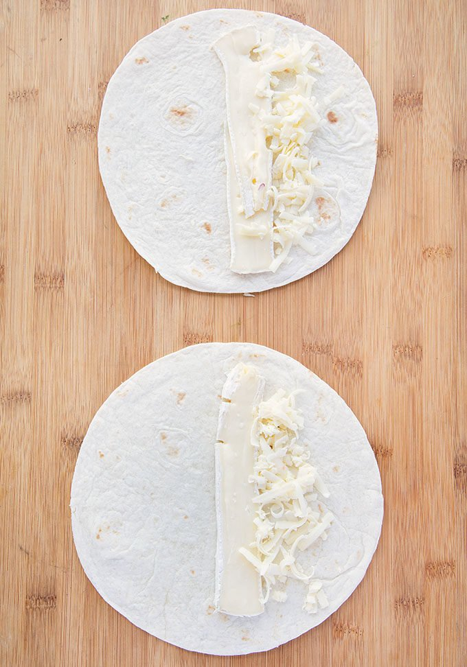 brie and shredded cheddar on two flour tortilla sitting on a wooden cutting board