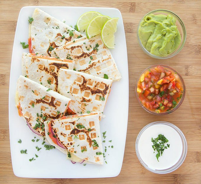 overhead view of smoked salmon quesadillas cut in half sitting on a white plate with a cilantro garnish sitting on a wooden cutting board with bowls of salsa, crema and guacamole