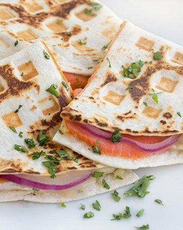 close up side view of smoked salmon quesadillas cut in half sitting on a white plate with a cilantro garnish