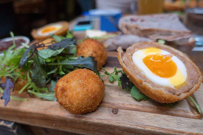 scotched eggs with one cut n half on a wooden cutting board with greens served at L. Mulligans Grocer in Dublin Ireland