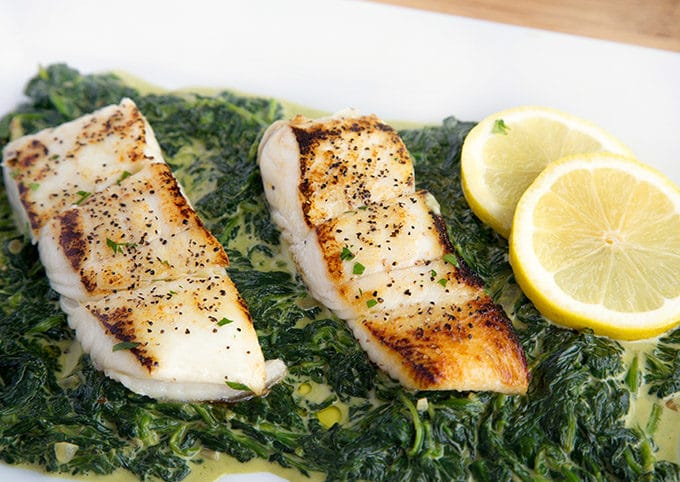 2 fillets of pan seared halibut sitting on a bed of creamed spinach on a white platter with 2 lemon slices in the upper right hand corner