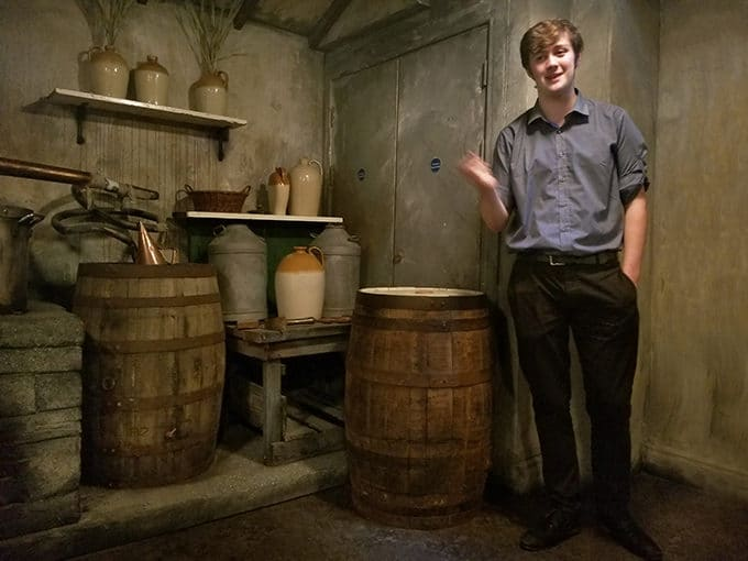 man standing in front of barrels in a cellar at the Whiskey Museum in Dublin Ireland