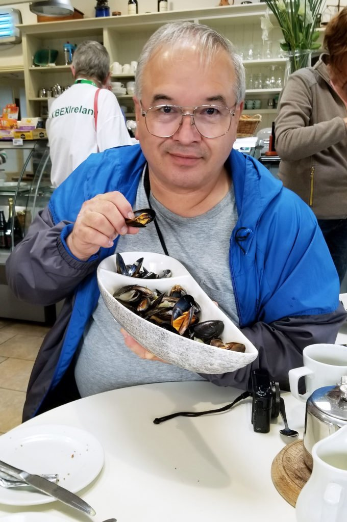 chef Dennis at a table with a white bowl of Mussels